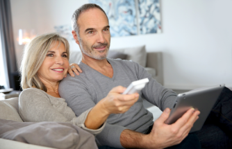 Image of a couple sitting on a couch with a remote in her hand and a tablet in his hands